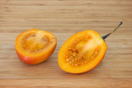 tomate de arbol: Primer plano de un tomate de árbol también conocido como tomate de árbol betaceum Solanum reducido a la mitad en una tabla de cortar de madera.