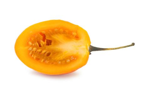 tomate de arbol: Primer plano de un tamarillo en rodajas también conocido como Solanum tomate de árbol betaceum visto desde el frente, aislado en fondo blanco. Foto de archivo