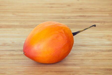tomate de arbol: Primer plano de toda una tamarillo también conocido como tomate de árbol Solanum betaceum sobre una tabla de cortar de madera. Foto de archivo