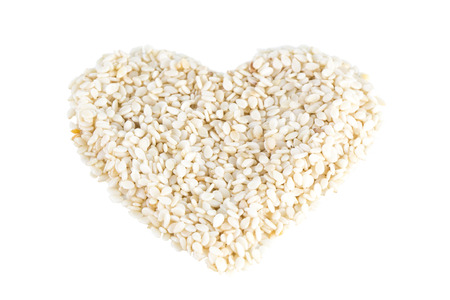 tilted: Heart shape made of sesame seeds with no shell, tilted angle, isolated on white background.