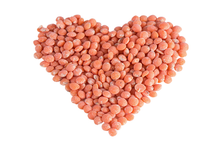 tilted: Heart shape made of red lentils, tilted angle, isolated on white background. Stock Photo