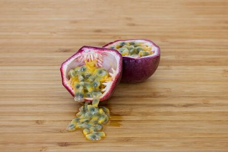 edulis: Close-up of a split passion fruit passionfruit, purple granadilla Passiflora edulis, seeds on a wooden table.