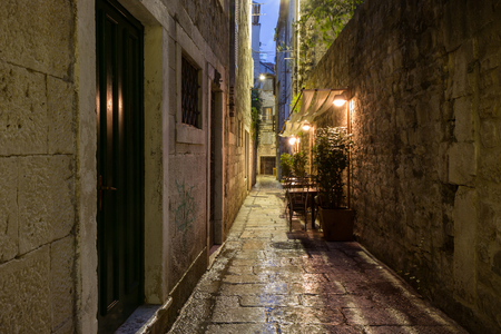 dark alley: Narrow and empty alley with few cafe tables at the old town in Split, Croatia, at dark after rain. Stock Photo