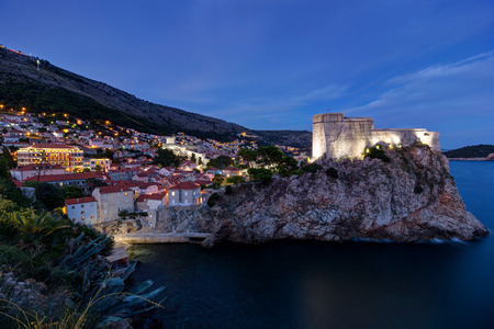 lawrence: View of Fort Lovrijenac St. Lawrence Fortress on top of a steep cliff and the city of Dubrovnik in Croatia at dark.