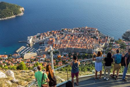 Toeristen op een uitkijkpunt te kijken naar de oude binnenstad van Dubrovnik in Kroatië van bovenaf.