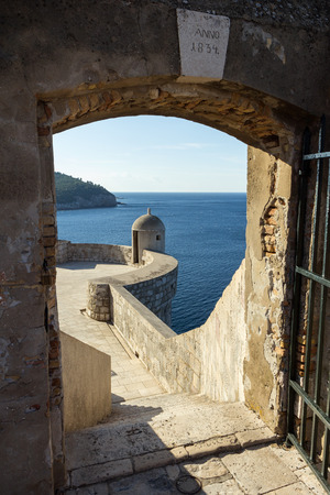 old towns: Open gate towards a small tower and ocean at the Old Towns city wall in Dubrovnik, Croatia.