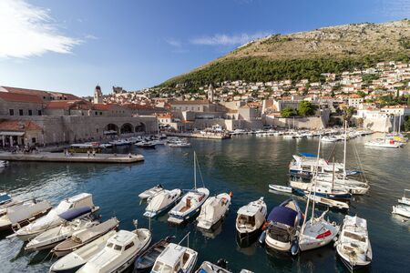srd: View of boats at the harbor in Dubrovniks Old Town and Mount Srd in Croatia.