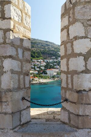 loophole: View of an ocean and city through a loophole at the City Walls in Dubrovnik, Croatia.