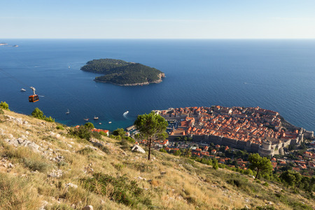 walled: View of a cable car, the walled Old Town of Dubrovnik and Lokrum Island in Croatia from above.