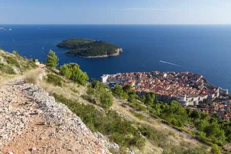 srd: View of a rocky path at the Mount Srd, the walled Old Town and Lokrum Island in Dubrovnik, Croatia from above. Stock Photo