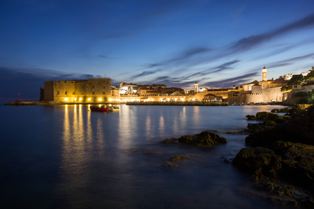 coastlines: Lit Old Town and rocky coast in Dubrovnik, Croatia at night.