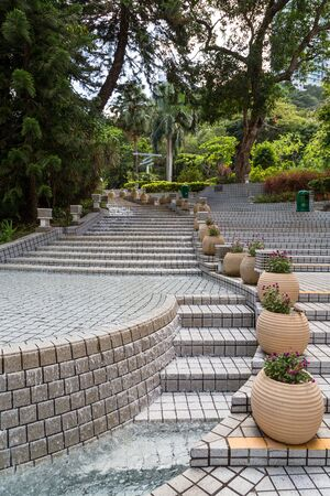 tourist feature: Water feature and empty stairs at the lush and green Hong Kong Park in Hong Kong, China.