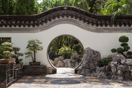 walled: Bonsai trees and Chinese style round doorway at the Kowloon Walled City Park in Hong Kong, China. Viewed from the front.
