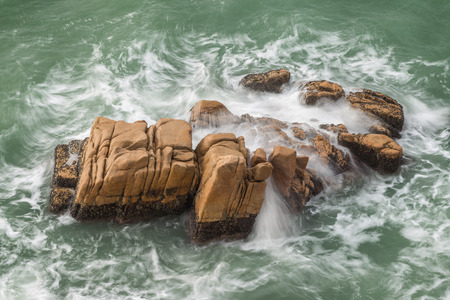 restless: Restless ocean and waves at a rock at the Cheung Chau Island in Hong Kong, China, viewed from above. Stock Photo