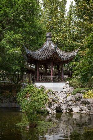 city park pavilion: Pond and small pavilion at the Kowloon Walled City Park in Hong Kong, China.
