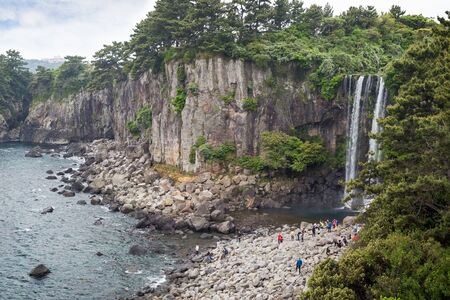 sea cliff: People at the Jeonbang Waterfall on Jeju Island in South Korea.