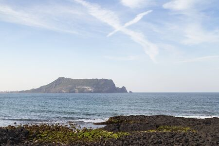 south space: Black lava rocks at the coast at Seopjikoji on Jeju Island in South Korea. Seongsan Ilchulbong is on the background. Copy space.