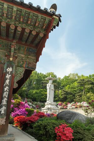 maitreya: Side of a building, lush vegetation and Mireuk Daebul statue (The Great Statue of Maitreya Buddha) at the Bongeunsa Temple in Gangnam, Seoul, South Korea.