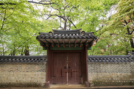 Verdant trees behind a wall and gate at the Changdeokgung Palace in Seoul, South Korea. Editorial