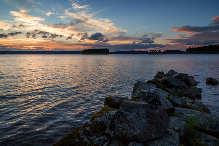 made in finland: View of an old and broken pier made of rocks and lake at sunset in Finland in the summer.