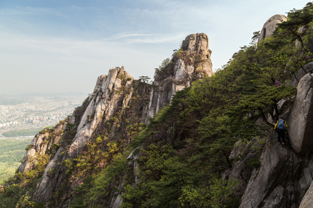 Man hiking on a steep cliff at the Jaunbong Peak on Dobongsan Mountain at the Bukhansan National Park in Seoul, South Korea. Stock Photo