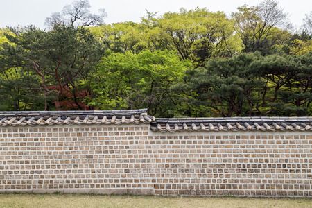 surrounding wall: Surrounding wall and trees behind at the Jongmyo Shrine in Seoul, South Korea, viewed from the front. Stock Photo