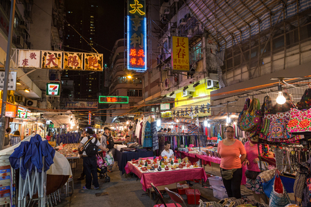 Tables and stalls full of all kinds of cheap merchandise being sold at the Temple Street Night Market in Kowloon, Hong Kong, China, at night. Its one of the liveliest night markets in Hong Kong and a popular tourist attraction.
