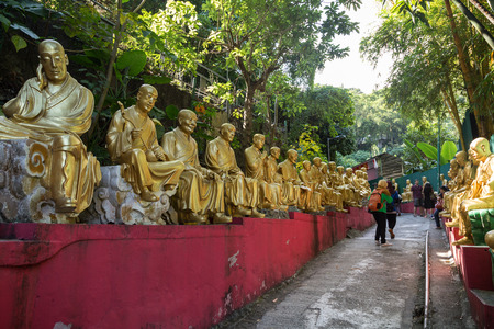 Tourists at the path to the Ten Thousand Buddhas Monastery (Man Fat Tsz) in Sha Tin (Shatin), Hong Kong, China. Path is lined with many golden Buddha statues each unique and in different poses. Editorial