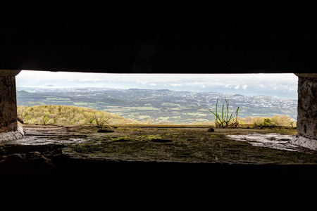 loophole: View through a loophole at a bunker atop the Eoseungsangak Peak on Jeju Island in South Korea. The bunker was built by the Japanese during the Pacific War in 1945. Stock Photo