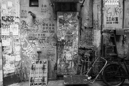 Graffiti, stickers and posters on a dirty and aged wall at some shady back street in Tsim Sha Tsui, Kowloon, Hong Kong, China.