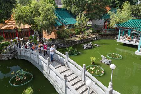 sin: People at a bridge and a pond at the Sik Sik Yuen Wong Tai Sin Temple in Hong Kong, China.