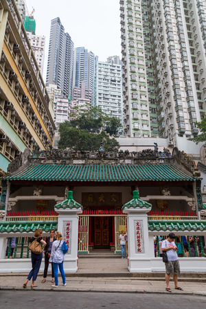 mo: People in front of the Man Mo Temple in Sheung Wan, Hong Kong, China. High-rise residential skyscrapers are behind it.