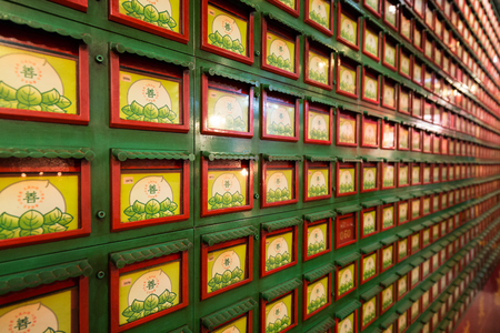 Close-up of a wall full of drawers that contain ashes of the deceased inside the Man Mo Temple in Sheung Wan on the Hong Kong Island in Hong Kong, China.