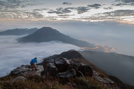 mountaintops: View of clouds, mountaintops, coastline and a man with a camera and tripod standing on a rock at the Lantau Peak on Lantau Island (the 2nd highest peak in Hong Kong, China) at dawn.