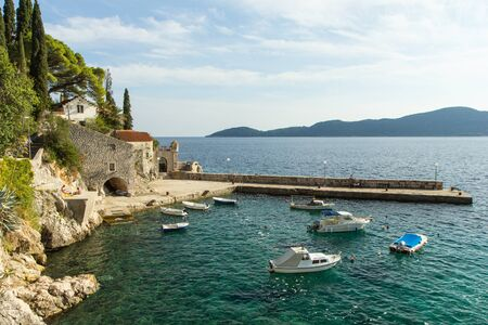 Picturesque view of a port with few people, boats and old buildings at a small town Trsteno in Croatia. Stock Photo