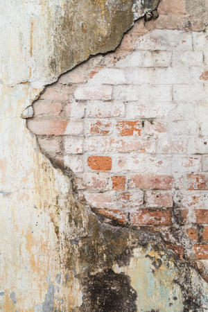 Broken old and dirty plastered wall revealing old brick wall.