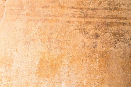 Weathered, aged and scratched orange concrete wall texture background.