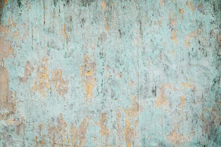 deteriorated: Weathered, faded and peeled off turquoise concrete wall texture background with vignetting.