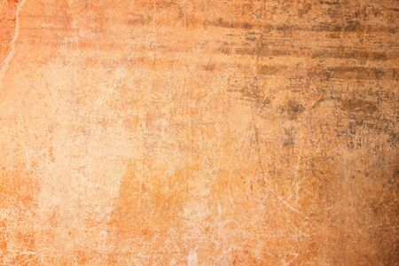 Weathered, aged and scratched orange concrete wall texture background with vignetting.