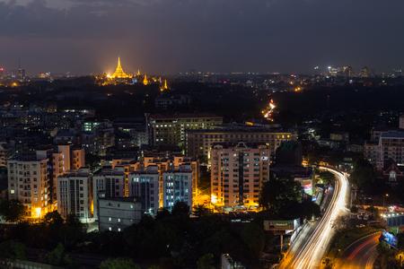 Uitzicht op Yangon, Myanmar, van bovenaf in de avond. Lit Shwedagon Pagoda ligt in de verte.