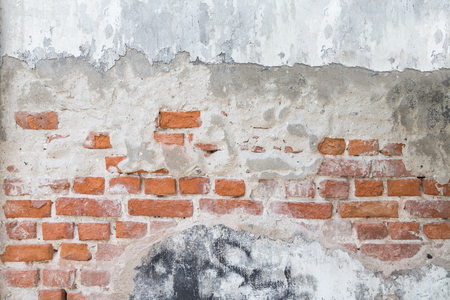 Broken, old and plastered wall revealing old brick wall. Stock Photo