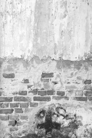 Broken, old and plastered wall revealing old brick wall in black&white.