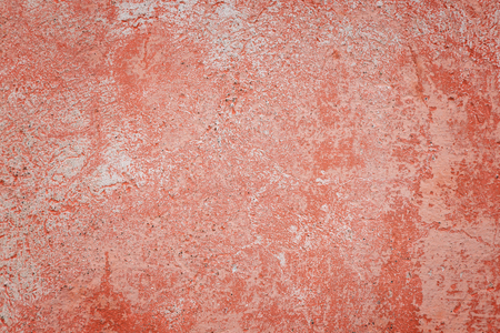 Close-up of a weathered and aged concrete wall with bleached red paint. Texture background with vignetting. Stock Photo