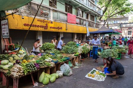 merchant: Many kind of fresh vegetables being sold and people at a street market on the 26th street in downtown Yangon, Myanmar (Burma).