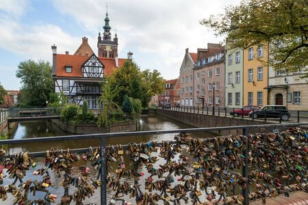 View of many love locks at the Love Bridge and Millers House (Dom Mlynarza) at the Mill Island on Raduni Canal in Gdansks Old Town in Poland. Its the old headquarters of the Millers guild. St. Cathrines Church is in the background.