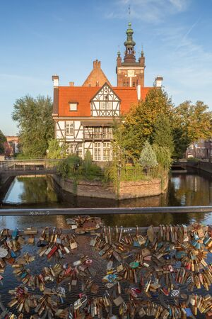 View of many love locks at the Love Bridge and Millers House (Dom Mlynarza) at the Mill Island on Raduni Canal in Gdansks Old Town in Poland on a sunny day. Its the old headquarters of the Millers guild. St. Cathrines Church is in the background.