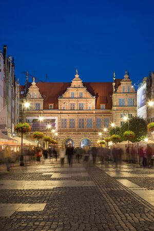 View of people and lit Green Gate at the Long Market, end of the Long Lane, at the Main Town (Old Town) in Gdansk, Poland, in the evening.