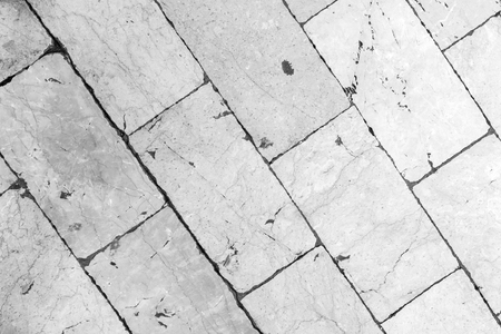 Close-up of a smooth paving at Stradun (or Placa), the main street in Dubrovnik, Croatia. Viewed from above in black and white.