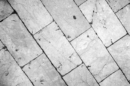 Close-up of a smooth paving at Stradun (or Placa), the main street in Dubrovnik, Croatia. Viewed from above in black and white with vignetting.