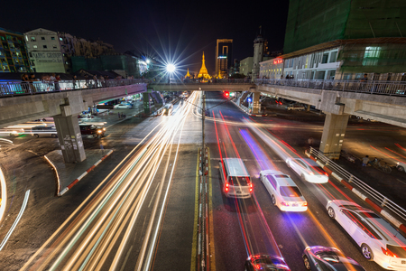 Traffics light trails and intersection of the Anawrahta and Sule Pagoda Roads at the downtown in Yangon (Rangoon), Myanmar (Burma) at night. Lit Sule Pagoda is in the background.